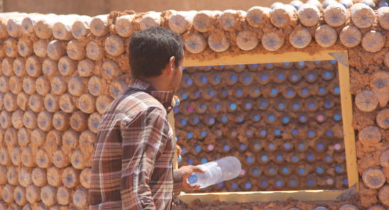 Building houses from sand-filled plastic bottles